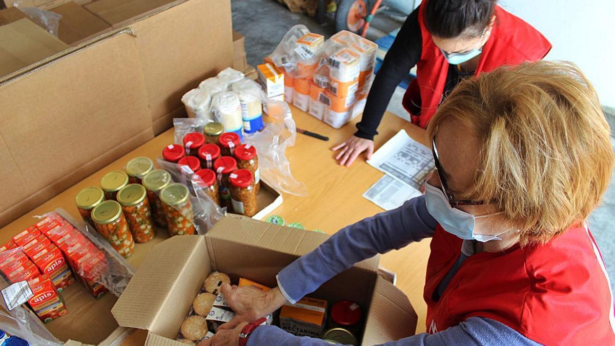 Voluntaris de Creu Roja preparant els lots que repartiran demà als usuaris del Rebost Solidari   ARNAU VALVERDE