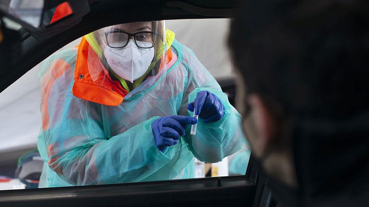 Una sanitaria explica a un hombre en Verín cómo recoger la muestra de saliva para la prueba.   | // BRAIS LORENZO