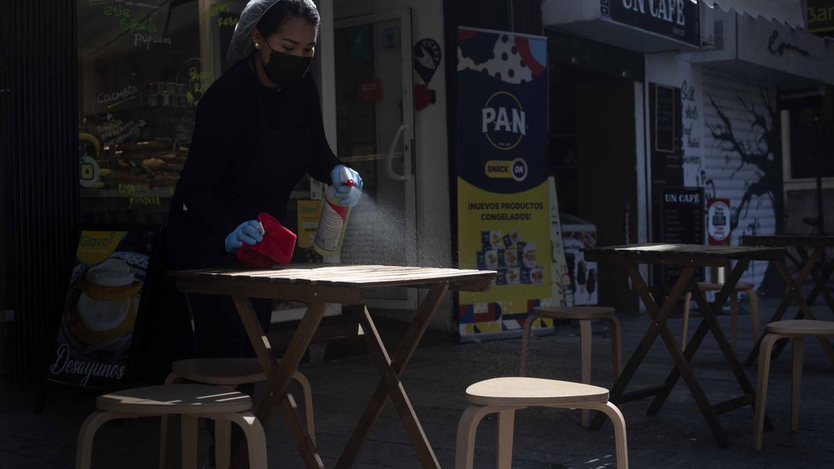 Una trabajadora desinfecta una mesa de un bar de València.
