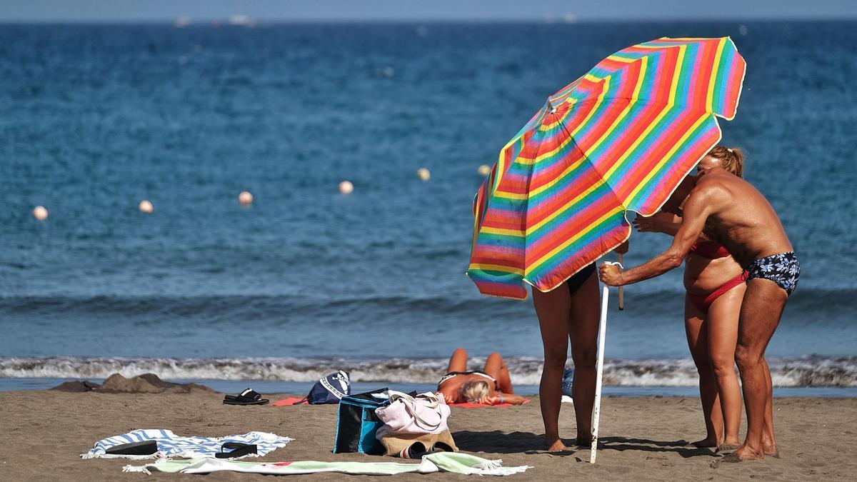 Unos turistas montan una sombrilla en Los Cristianos, en el municipio tinerfeño de Arona.