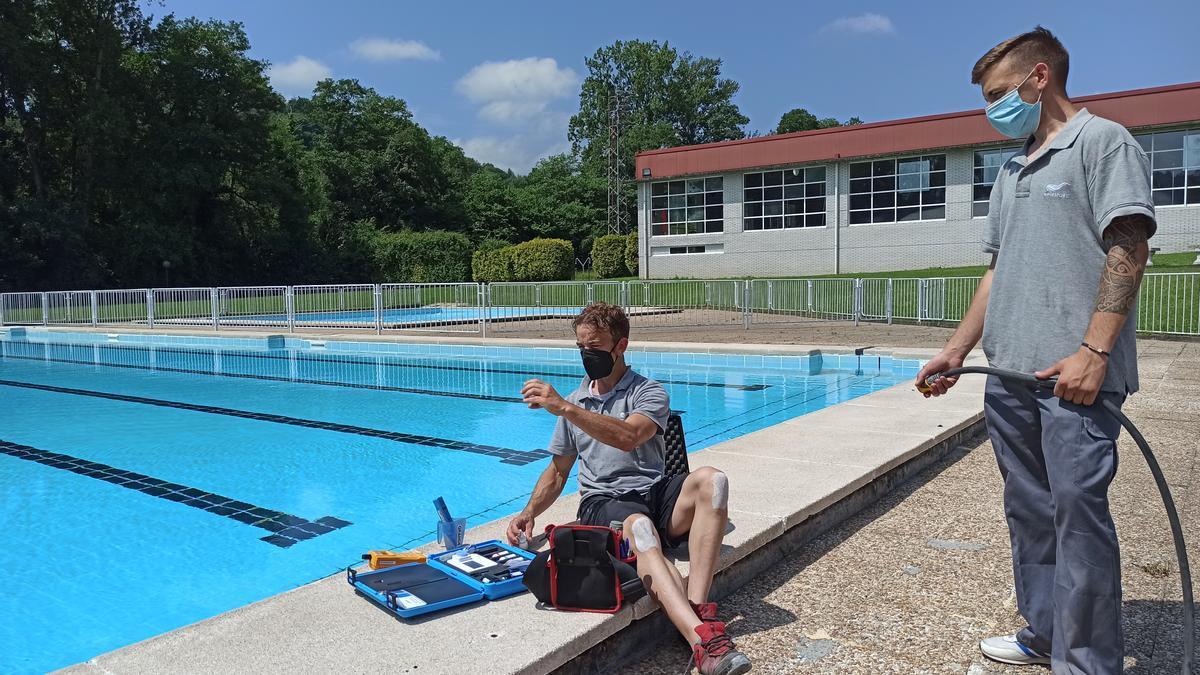 Jorge Jose y Gorka Feito, trabajadores de la piscina, comprueban el estado del agua con un análisis