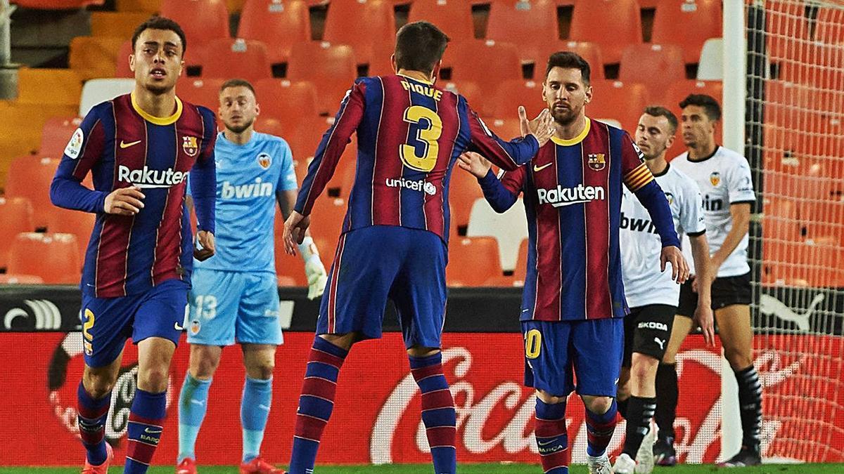 Piqué felicita a Messi anoche en Mestalla. |  // EUROPA PRESS