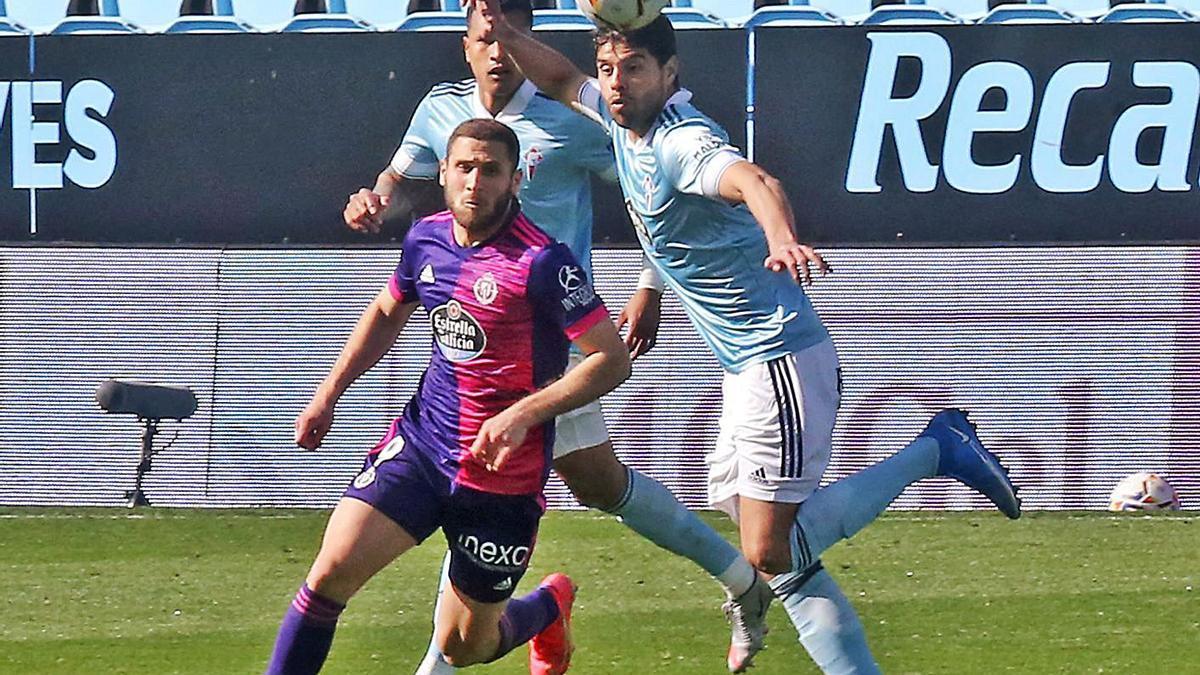 Néstor Araújo despeja el balón ante la presencia de un jugador del Valladolid. |  // MARTA G.BREA