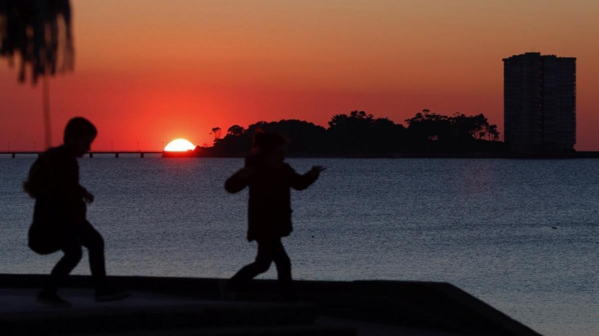 Niños jugando durante una puesta de sol en Vigo. // J. Lores