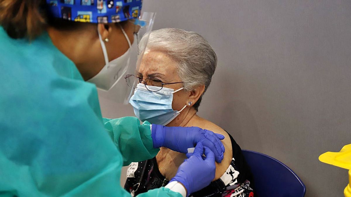 Una enfermera pone una tirita tras administrar una dosis.