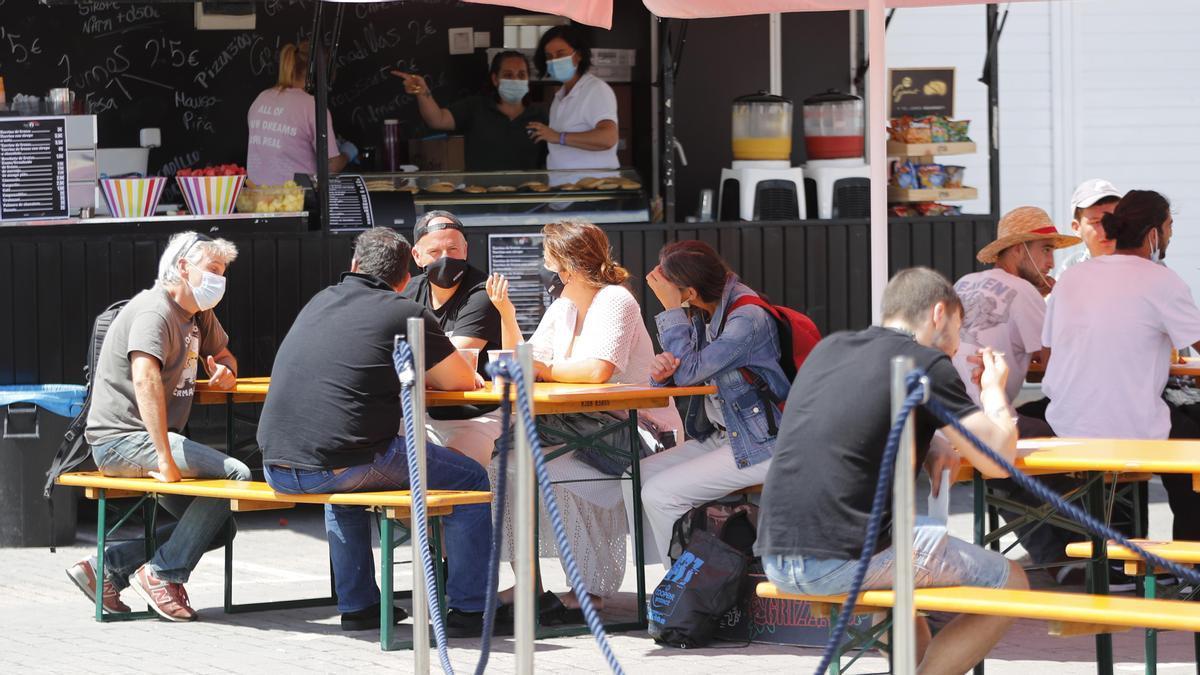 """Comensales con la mascarillas puestas ante un """"food truck"""" en O Mariquisiño, el pasado fin de semana en Vigo."""