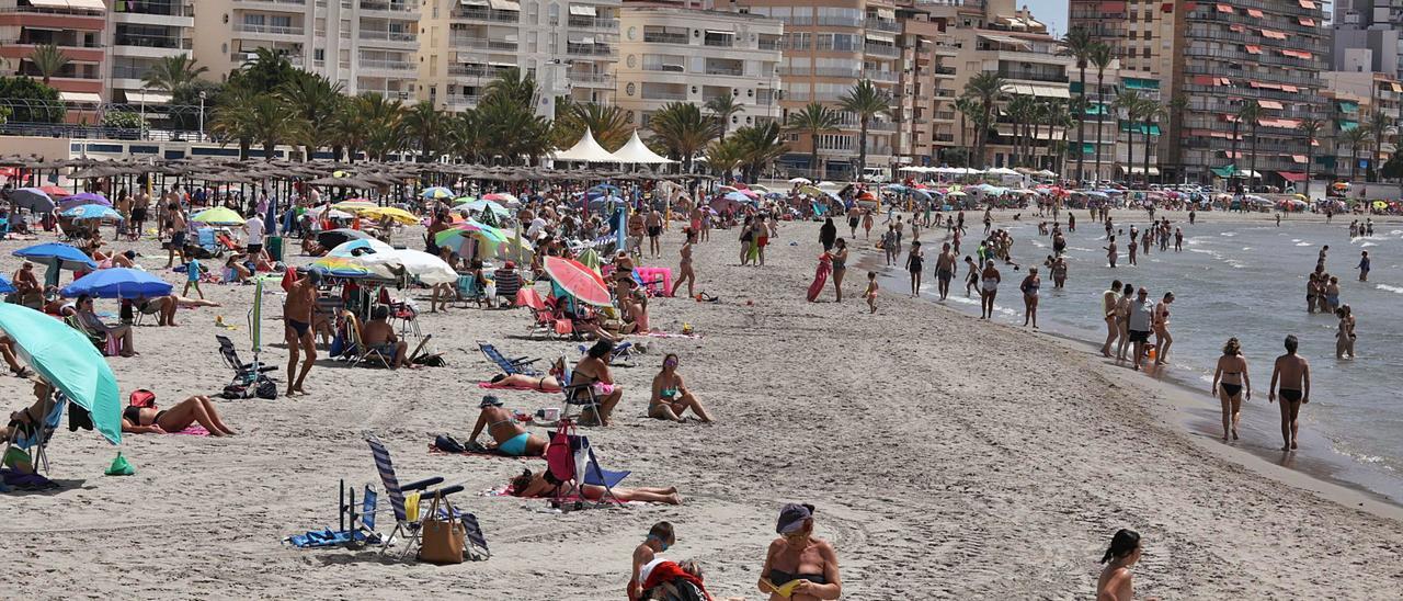 Bañistas y usuarios de otras instalaciones en las playas de Santa Pola, El Campello y Benidorm, municipios con más visitantes dominicales este verano que en julio de 2020. | A.AMORÓS/P.CORTÉS/D.REVENGA