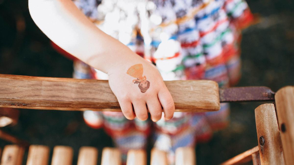 Imagen de recurso de una niña con una calcomanía en la mano.