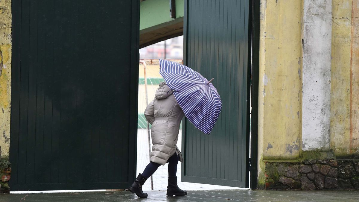 Una persona con paraguas por el paseo marítimo de A Coruña.