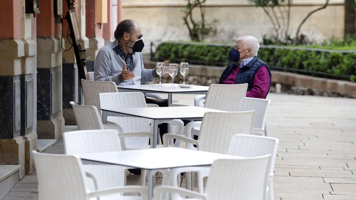 Dos clientes toman algo en una terraza de la capital