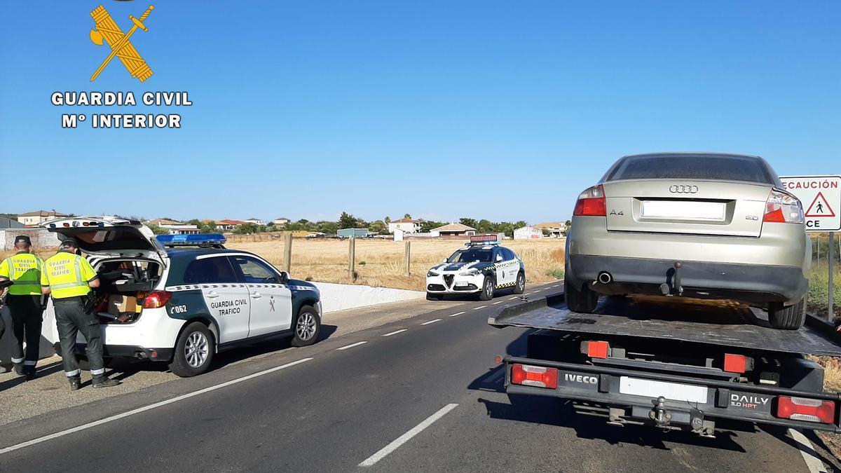 La Guardia Civil, junto al coche ya subido a una grúa para su retirada.