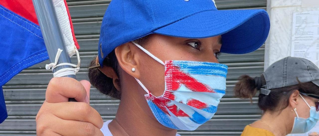 Una manifestante con una bandera de Cuba durante la protesta.