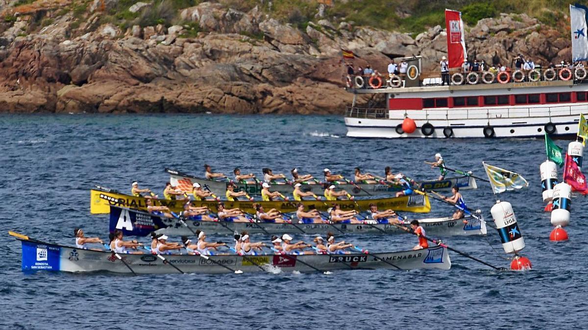 Arriba, salida de la regata femenina. Abajo, el público sigue la prueba desde paseo y rocas. |  // CARLOS PARDELLAS