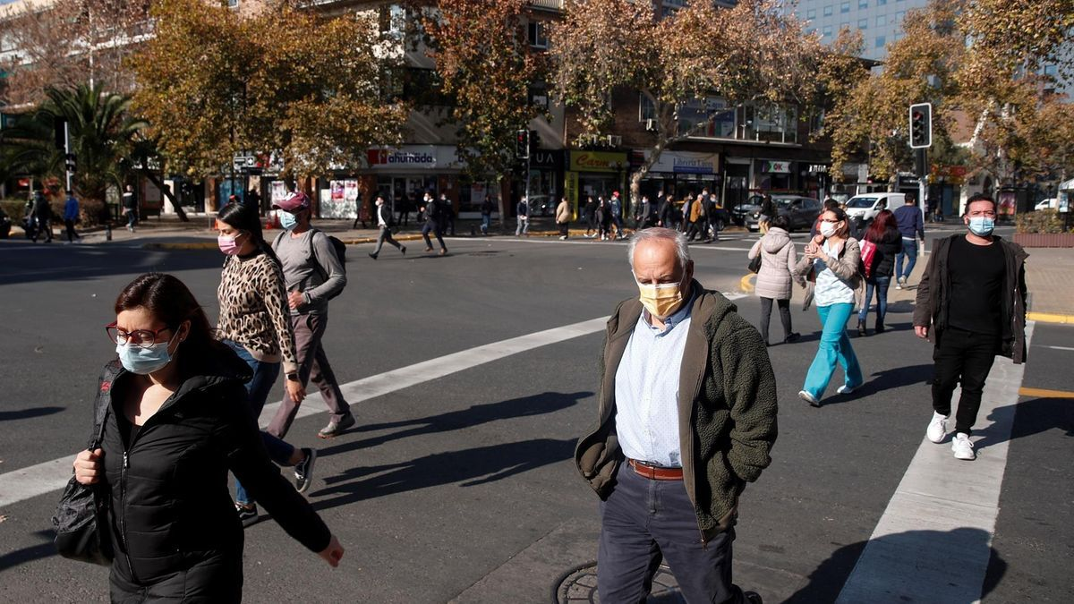Peatones caminan con mascarilla en una calle