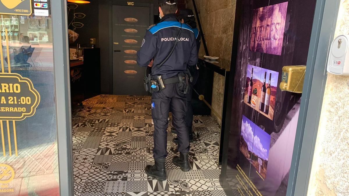 Dos agentes de la Policía Local inspeccionan un establecimiento de hostelería