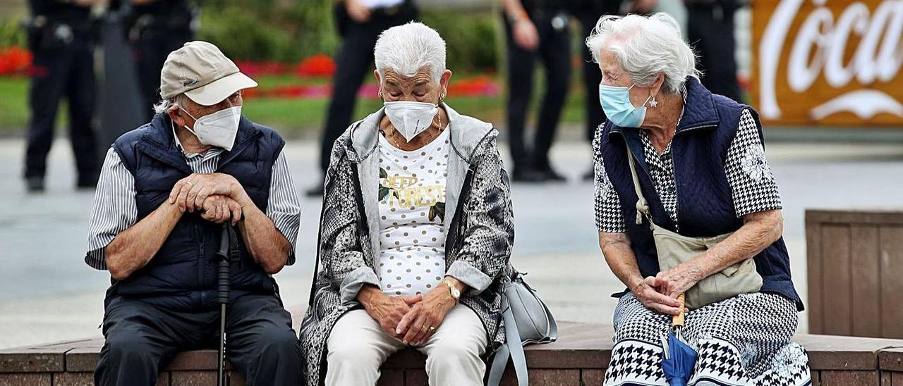 Un grupo de personas mayores, de charla y protegidos con mascarillas.