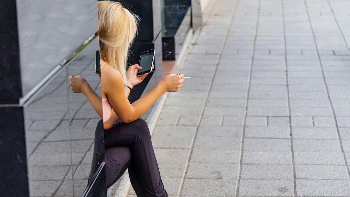 Una joven fumando en la calle.