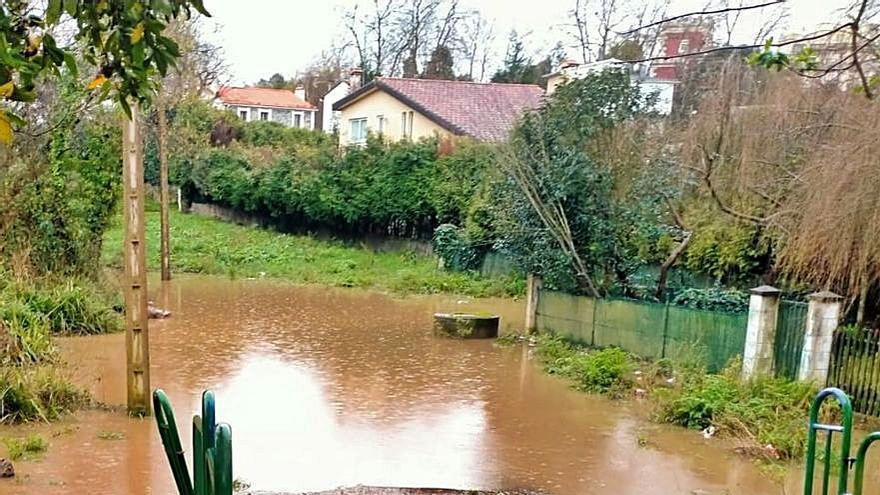 La rúa do Saber junto al colegio, embarrada tras quedar inundada