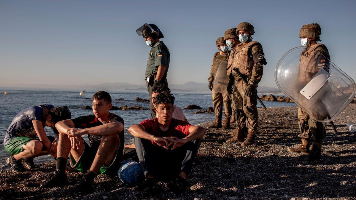 Miembros del Ejército observan a un grupo de migrantes en el espigón del Tarajal