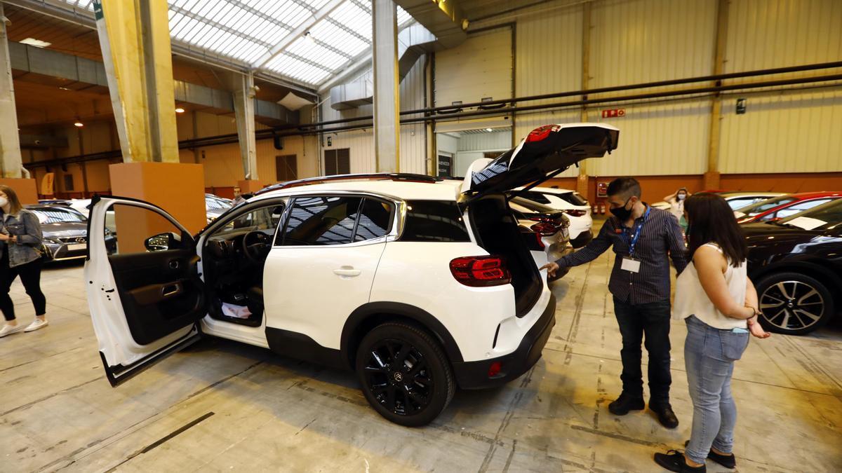 Un comercial enseña un coche a un cliente en la feria Stock Car de Zaragoza