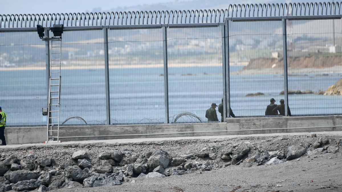 Agentes de la Gendarmería marroquí levantan alambradas de concertinas en el espigón del Tarajal