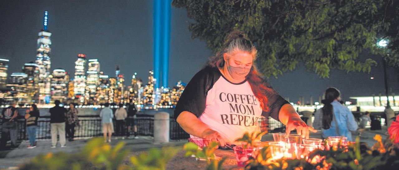 Un grupo de gente enciende velas en recuerdo de las víctimas del 11-S. Al fondo, un tributo de luz instalado en el One World Trade Center por el vigésimo aniversario de los atentados.