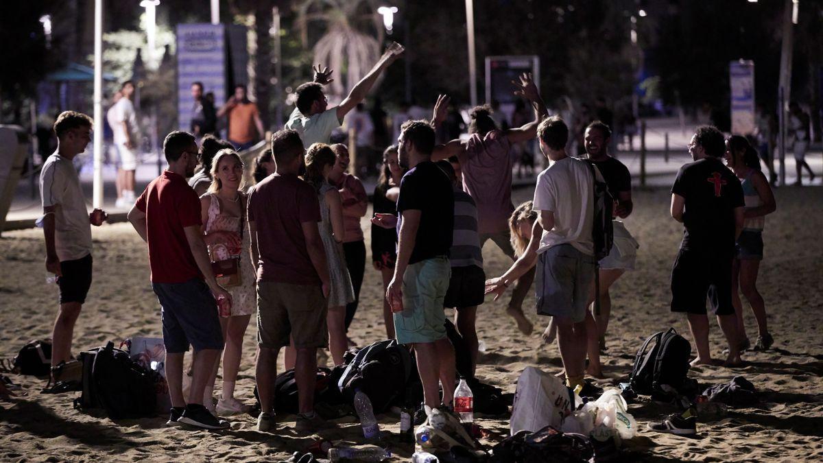 Jóvenes celebran un botellón en la playa.