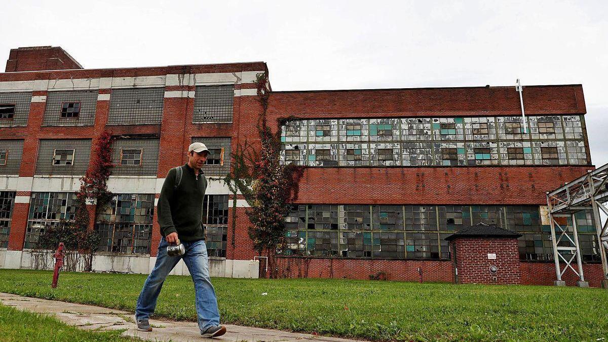 Un habitante de Warren pasa delante de una fábrica abandonada.
