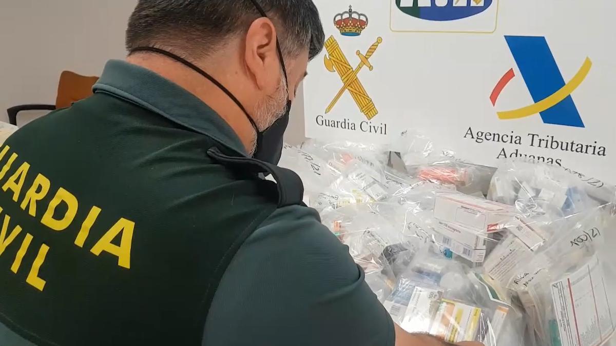 Un agente de la Guardia Civil con los medicamentos intervenidos en el aeropuerto de Palma.