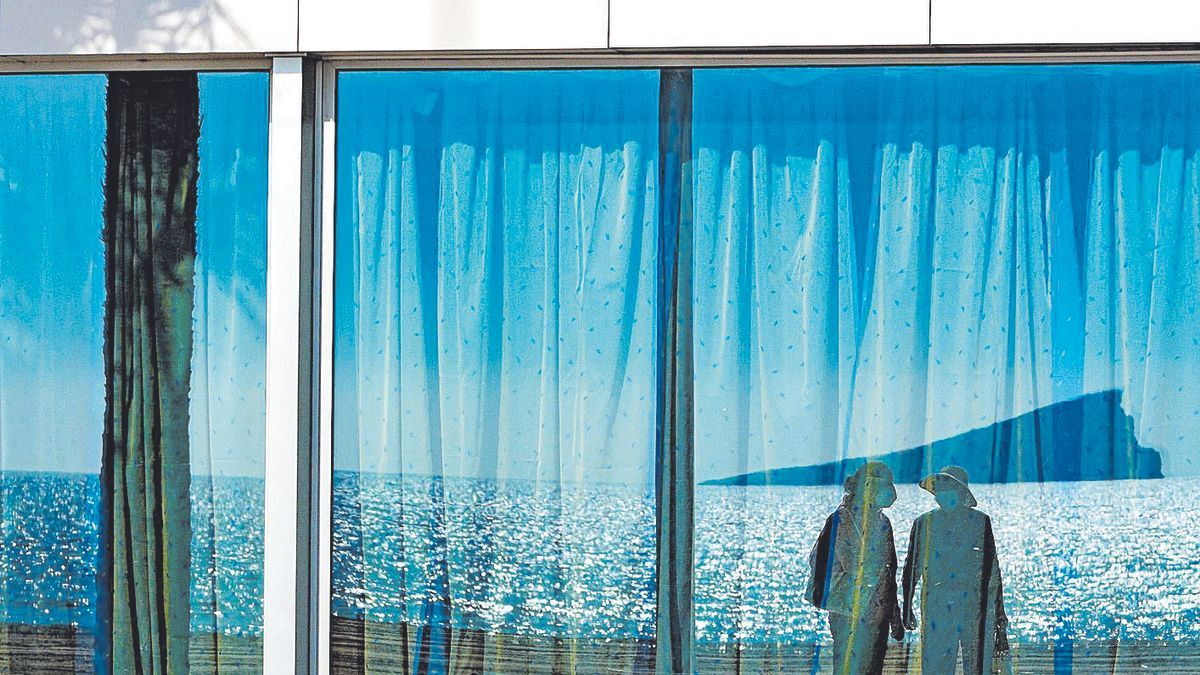The island of Benidorm reflected in the facade of a restaurant.
