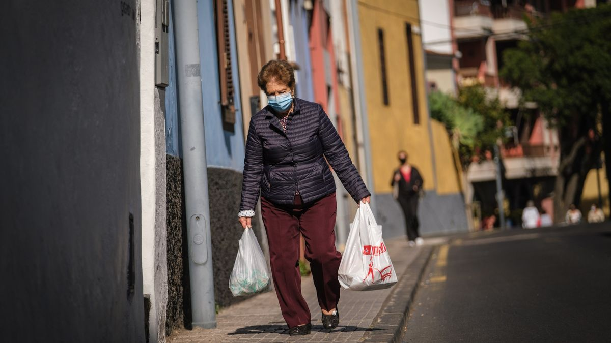 Una mujer con mascarilla camina por una calle de La Laguna.