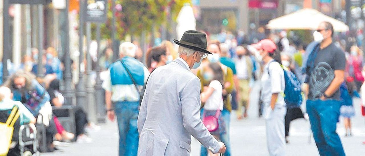 Un señor con bastón pasea por la calle Triana, en la capital grancanaria.