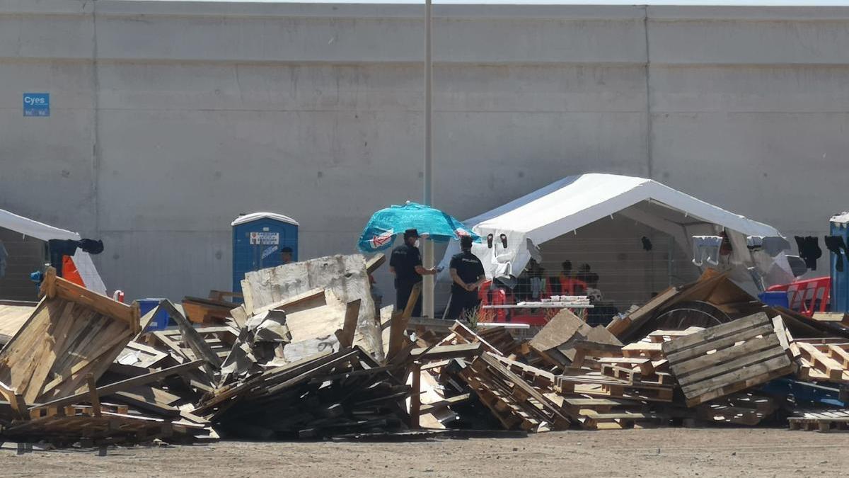 Agentes bajo una sombrilla junto a las carpas de Cruz Roja para los extranjeros.