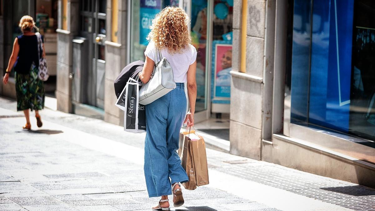 Una mujer camina con bolsas por la calle Castillo de Santa Cruz.