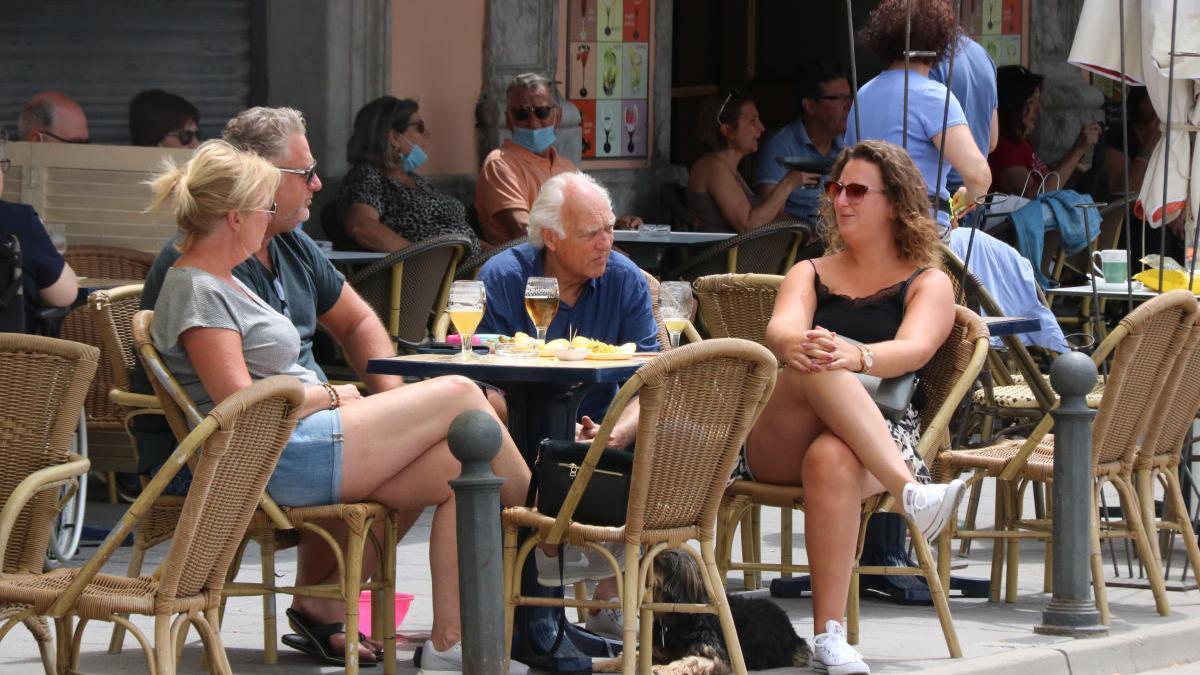 Un grup de persones prenen una cervesa en una terrassa.