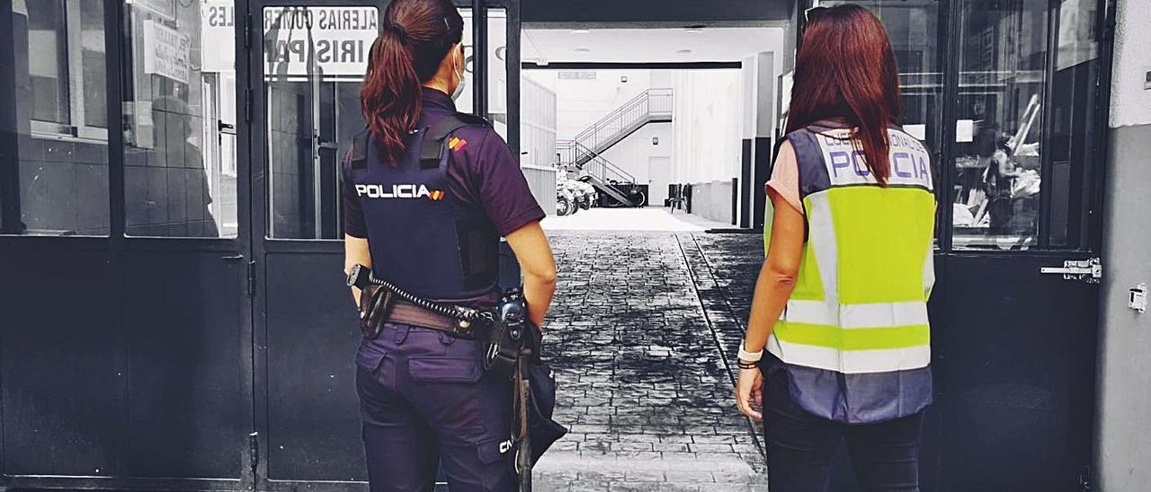 Dos policías en la puerta de la Comisaría que ha investigado los daños en la vivienda.