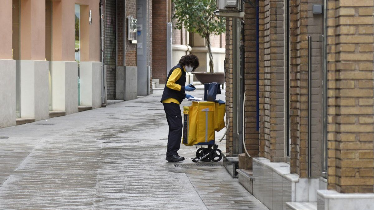 Una trabajadora de Correos reparte la correspondencia con guantes y mascarilla.