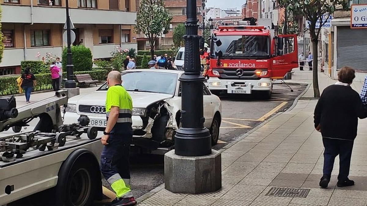 La grúa retira el coche accidentado en la calle Álvaro Flórez Estrada. | LNE