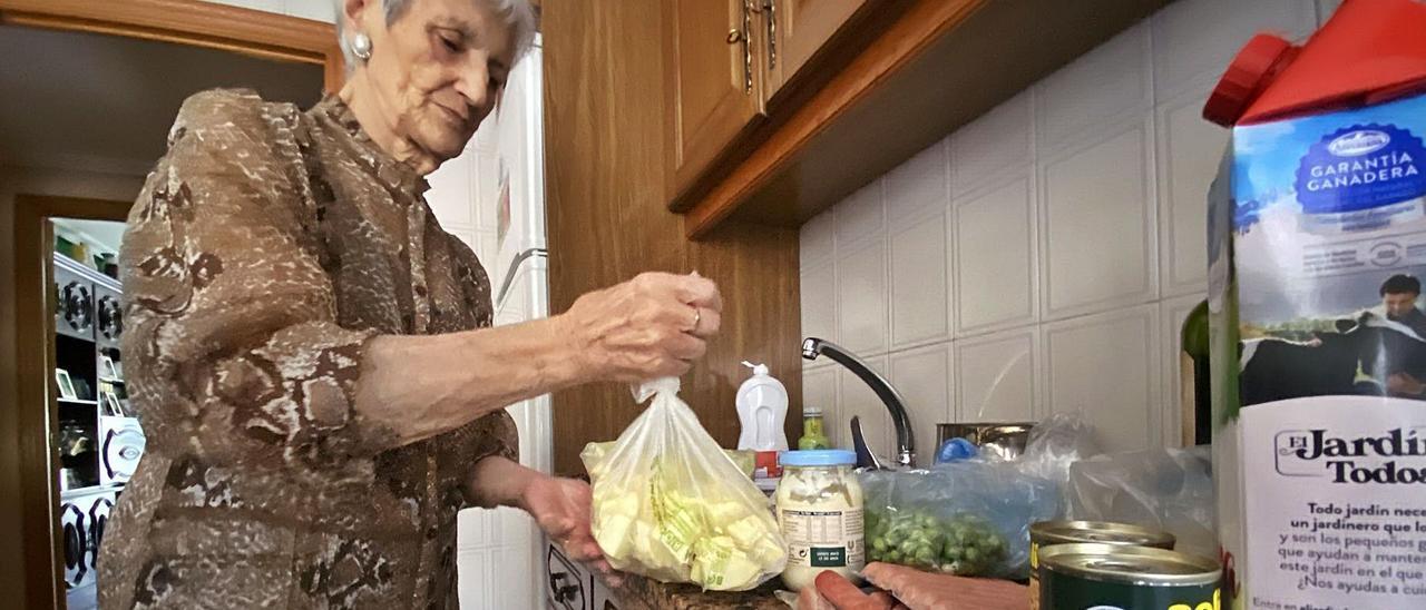 María Luisa Morán Fueyo saca la comida de la nevera para tirarla, tras cuatro días sin suministro eléctrico.   C. M. B.