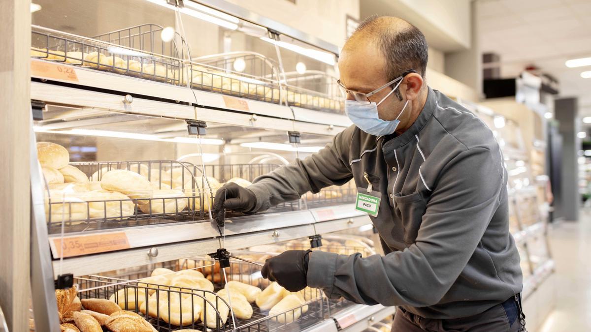 Un trabajador repone el pan en un supermercado.
