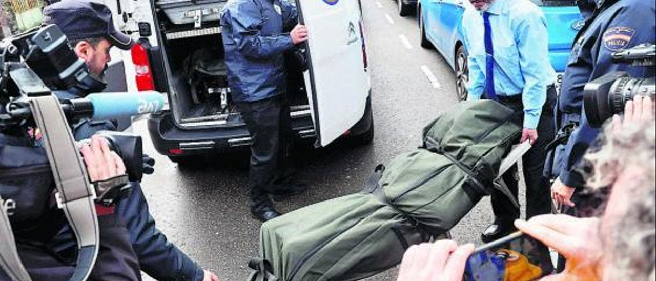 Operarios de la funeraria trasladan el cadáver de la víctima. | J. L. Cerejido