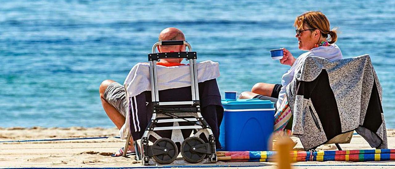 Una pareja disfruta de la playa de Levante  en Benidorm este invierno.  
