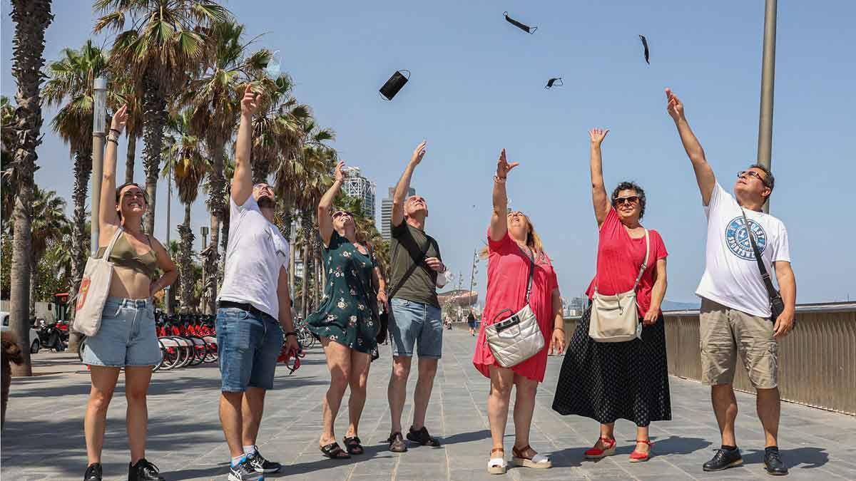 Un grupo de gente en el paseo Marítim de Barcelona lanza sus mascarillas al aire.