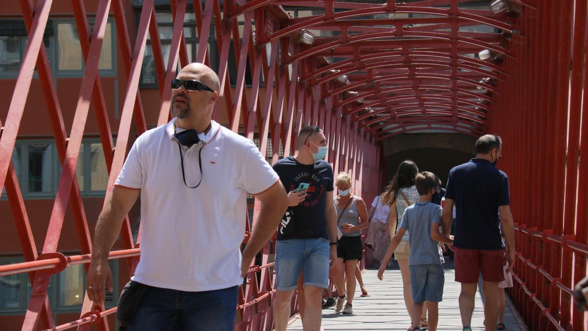 Diverses persones passejant amb mascareta pel Pont Effiel.