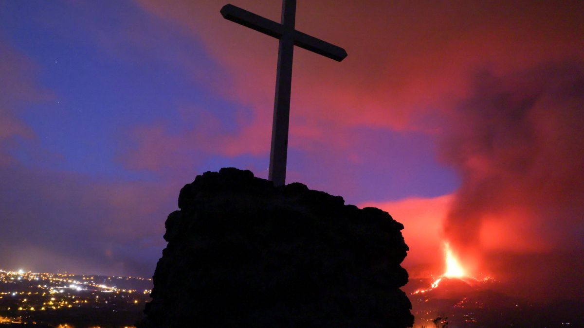 A cross is seen as lava and smoke rise following the eruption of a volcano on the Island of La Palma