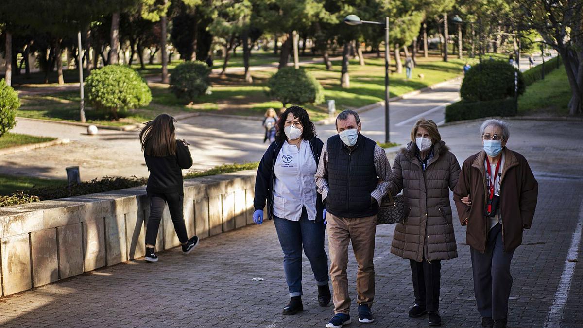 Residentes del centro de mayores Jardines del Palau de València salen a pasear por el cauce del río tras meses aislados. | GERMÁN CABALLERO