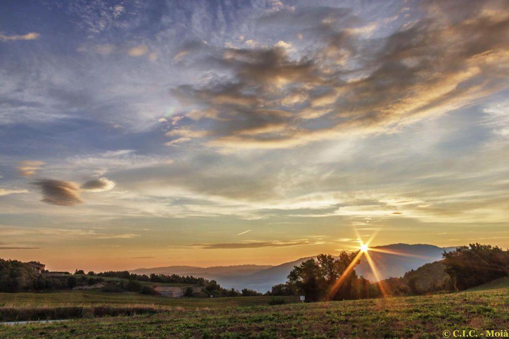 El sol surt per darrere les muntanyes al Moianès.
