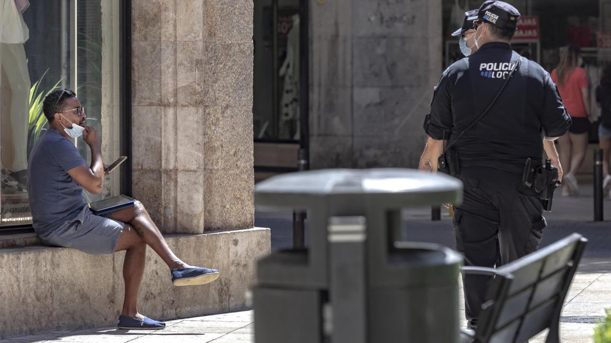 Agentes de la Policía Local controlan el uso de la mascarilla en Palma.