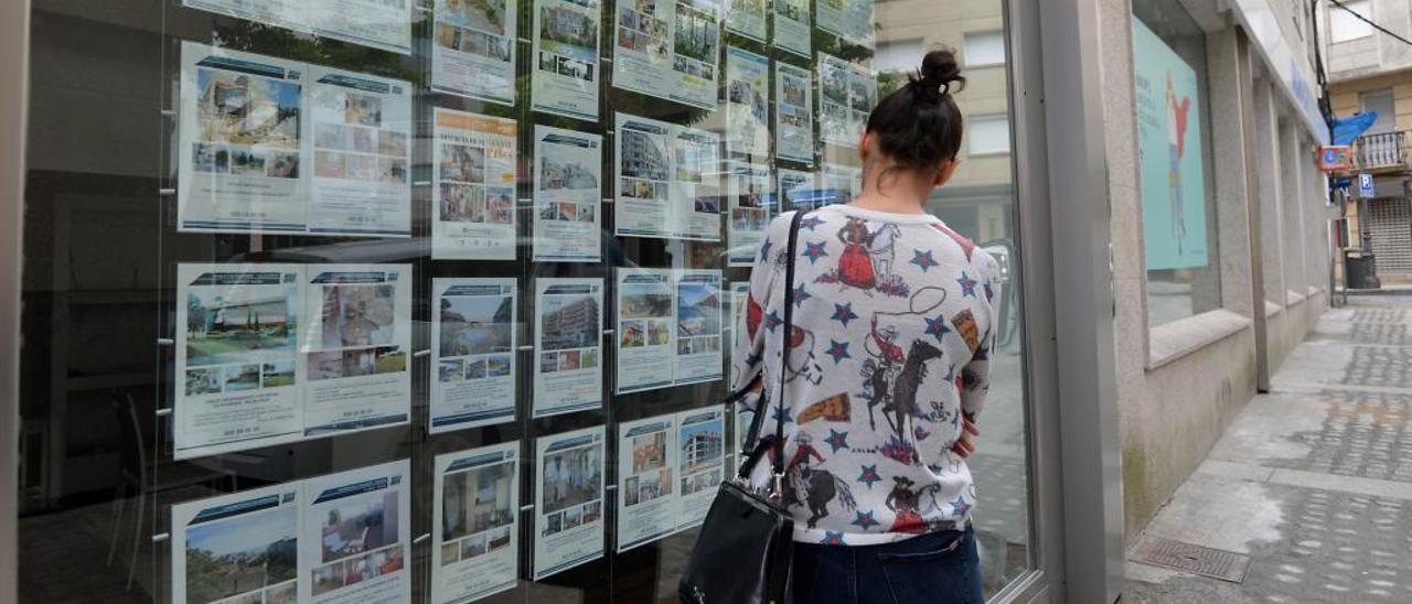 Una joven mira el escaparate de una inmobiliaria