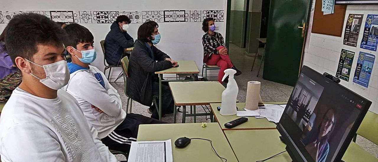 Los alumnos Daniel Arturo Britos y Enrique Vijande, ayer, siguiendo la ponencia de Carmen Molejón.   Reproducción de D. Á.